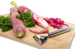 Red radish, parsley and a peeler on a wooden cutting board. Isolated on white Stock Photography