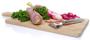 Red radish, parsley and a peeler on a wooden cutting board. Isolated on white Royalty Free Stock Images