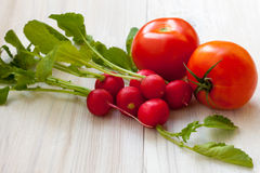Red radish and tomato. Healthy red radish and tomato on the table Stock Photos