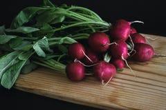 Red radish on wooden board in dark. Ness Stock Photos