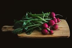 Red radish on wooden board in dark. Ness Royalty Free Stock Images