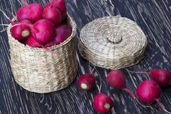 Red radishes in a basket. Red radishes in a basket on wooden desk Stock Photo