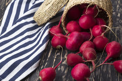 Red radishes in a basket. Red radishes in a basket on wooden desk Royalty Free Stock Photography