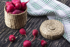 Red radishes in a basket. Red radishes in a basket on wooden desk Royalty Free Stock Images