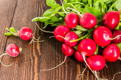 Red radishes in bowl on wooden table. Vegetable of cabbage family. Horizontal photo Royalty Free Stock Photos