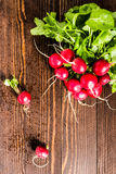 Red radishes in bowl on wooden table. Vegetable of cabbage family. Top view vertical photo Stock Images