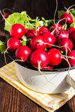 Red radishes in bowl on wooden table Royalty Free Stock Photo