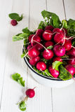 Red radishes in bowl on wooden table. Vegetable of cabbage family. Vertical photo Royalty Free Stock Photography