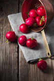 Red radishes in a colander on a wooden table. Vertical Stock Photo