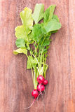 Red radishes over wood cutting board. Organic, small, red radishes, freshly harvested from home grown garden.  over a brown wood background Royalty Free Stock Images