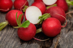 Red radishes some cut in two. On wooden surface Royalty Free Stock Photo
