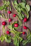 Red radishes spread on rustic board. Bunch of organically grown, freshly harvested, red radishes, arranged and  over rustic wooden background, close up, top view Stock Photography