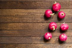Red radishes on wooden table with copy space. Red, raw, whole radishes on dark brown wooden table. Copy space. Objects in right position. Close up. Horizontal royalty free stock photo