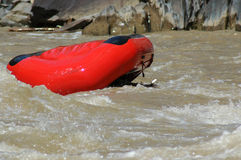 Red raft floating upside down in rapids Royalty Free Stock Photo