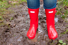 Red Rain Boots. Bright shining clean red rain boots on a girl while she stands in the mud puddle Stock Images