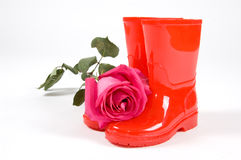 Red rain boots with a pink rose Royalty Free Stock Image