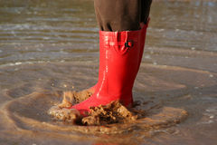 Red rain boots in puddle. Red rain boots splashing around in mud puddle Royalty Free Stock Photography