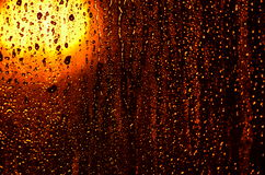 Heavy rain on window. Heavy rain droplets running on the window glass lit by orange halogen street lamp Stock Image