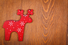Red raindeer on wooden background Royalty Free Stock Images