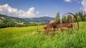 Red rake in a field in the mountains Stock Photography