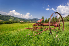 Red rake in a field in the mountains Stock Photo