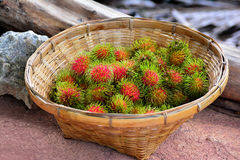 Red rambutan is in a basket. On a cement floor and  the old Timber is Behind Royalty Free Stock Photography