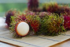 Red rambutans on wooden table. Ripe delicious red rambutans on wooden table Stock Photo
