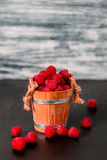 Red raspberries in a basket on black wooden background. Close up. Stock Image
