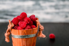 Red raspberries in a basket on black wooden background. Close up. Royalty Free Stock Photography