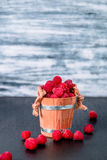 Red raspberries in a basket on black wooden background. Close up. Copy space. Royalty Free Stock Image