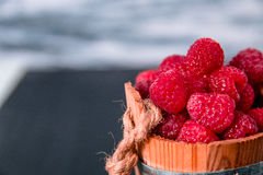 Red raspberries in a basket on black wooden background. Close up. Copy space. Stock Image