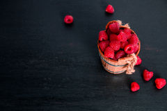 Red raspberries in a basket on black wooden background. Frame. Copy space. Top view. Stock Images