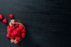 Red raspberries in a basket on black wooden background. Frame. Copy space. Top view. Royalty Free Stock Photos