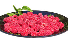 Red raspberries on a black plate on a white background Royalty Free Stock Photo