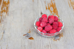 Red raspberries in bowl on wooden background Royalty Free Stock Photography
