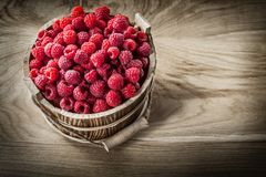 Red raspberries in bucket on wooden board top view.  Stock Photo