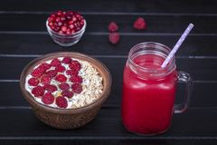 Raspberries juice in a glass mug and muesli made from raw raspberry, oat flakes, chia seeds with yogurt and honey on black wooden. Red raspberries juice in glass Stock Photos