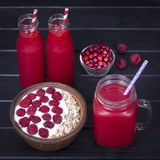 Raspberries juice in a glass mug and muesli made from raw raspberry, oat flakes with yogurt and honey on black wooden background,. Red raspberries juice in glass Stock Photo