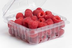 Red raspberries in plastic container Stock Photo
