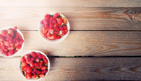 Red raspberries in a plate with strawberries on a old wooden bac Stock Image