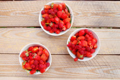 Red raspberries in a plate with strawberries on a old wooden bac Stock Images