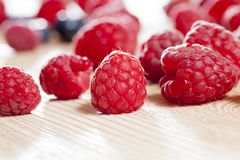 Red raspberries. Red ripe raspberries lying on an old wooden table of light color. small depth of field, close-up photo Stock Photo