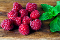 Red raspberries and a sprig of fresh green mint Stock Photos