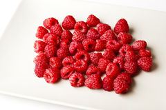 Red raspberries on white plate Stock Photography