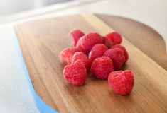 Red raspberries on a wooden board royalty free stock photo