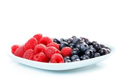 Red raspberry and black bilberry. In  plate,  on white Royalty Free Stock Photography