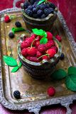 Red raspberry and  blackberry with leaf in a basket on vintage metal tray. Red raspberry and  blackberry with leaf in a basket on vintage metal tray Royalty Free Stock Photo