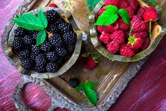 Red raspberry and  blackberry with leaf in a basket on vintage metal tray. Top view. Stock Image