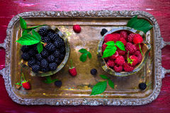 Red raspberry and  blackberry with leaf in a basket on vintage metal tray. Top view. Red raspberry and blackberry with leaf in a basket on vintage metal tray Royalty Free Stock Photos