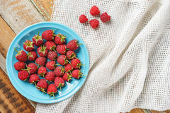 Red raspberry in blue dish and in front of white fabric on old vi Royalty Free Stock Image